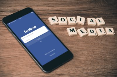 Image shows Facebook open on a smartphone with Scrabble game tiles next to it spelling out Social Media